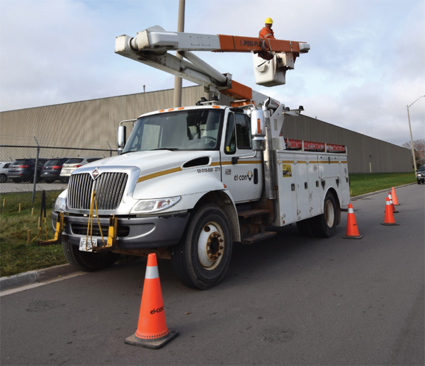 Photo of El-Con Construction Inc. work crews performing overhead streetlight maintenance using aerial lift truck.