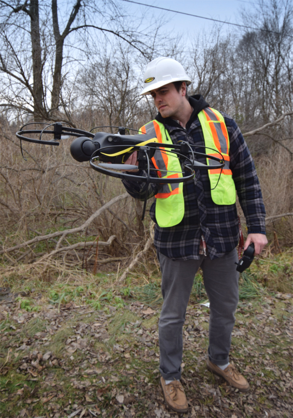 Photo of Huron Geomatics Inc. employee in the field launching aerial drone.